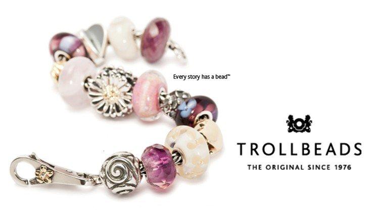 Locandina pubblicitaria Trollbeads su sfondo bianco con un bracciale con perline sui toni del rosa