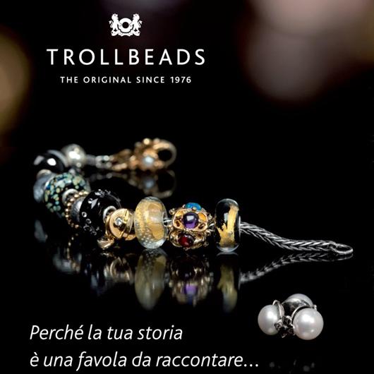 Locandina Trollbeads a sfondo nero con un bracciale con perline colorate
