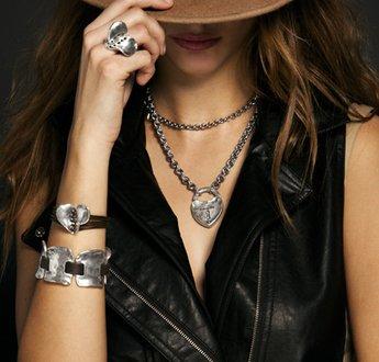 Locandina pubblicitaria con ragazza con giubbino di pelle, un cappello e gioielli alle braccia, mani e collo