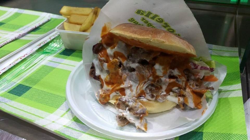 un panino con carne, ketchup e salsa yogurt