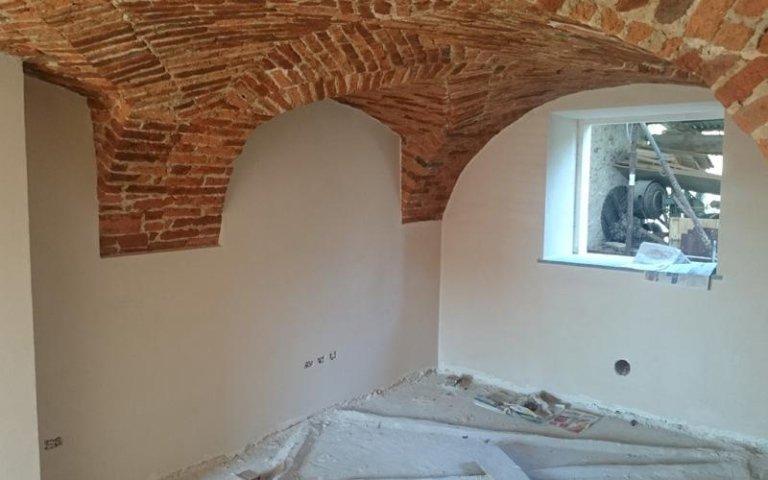 interno di una villa in ristrutturazione con un arco di mattoni a vista che funge da soffitto