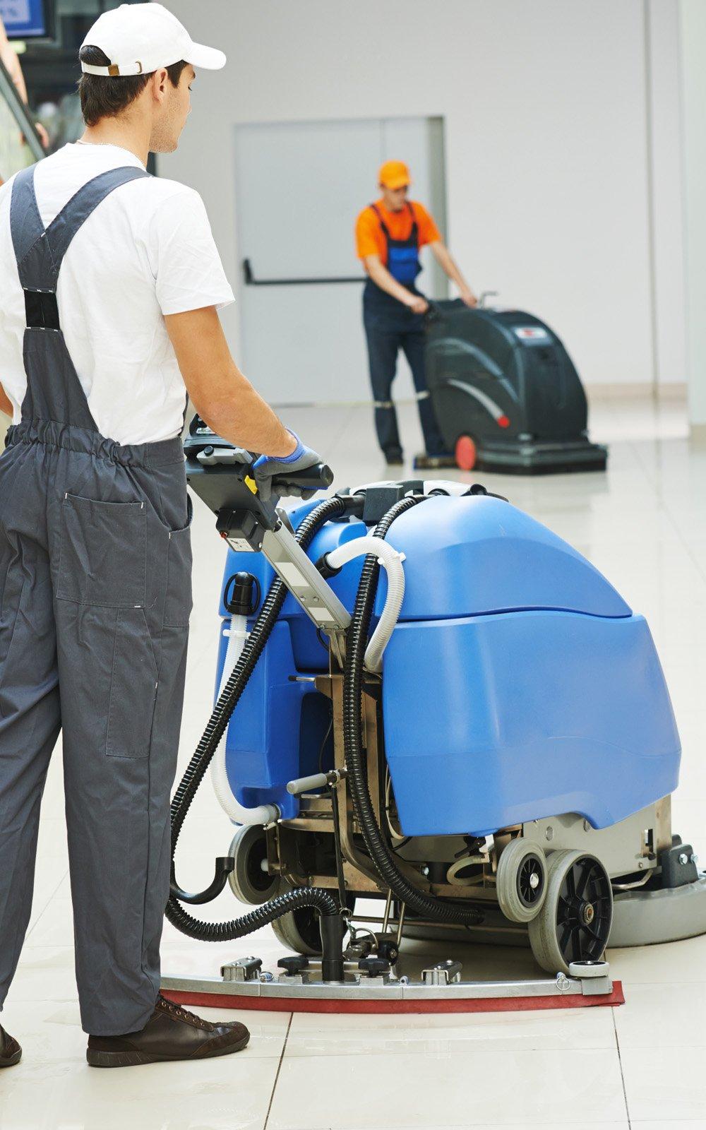 Due operai puliscono un pavimento con dei macchinari