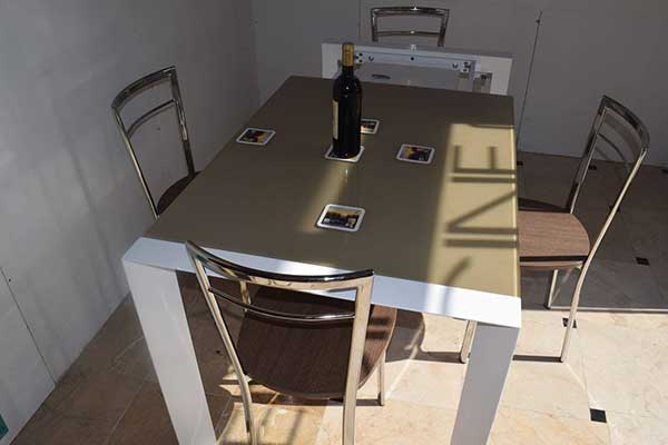 tavolo di cucina con sedie e una bottiglia appoggiata sopra