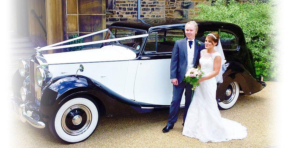 couple next to wedding car