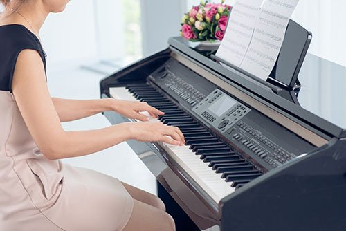 Young girl practicing on piano