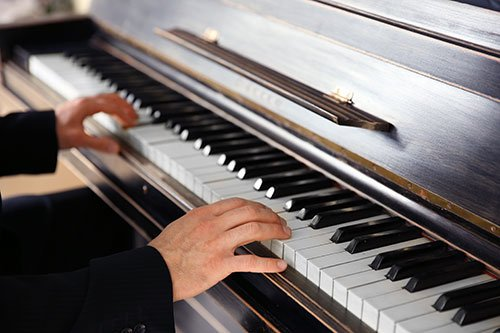 Young individual practicing on piano