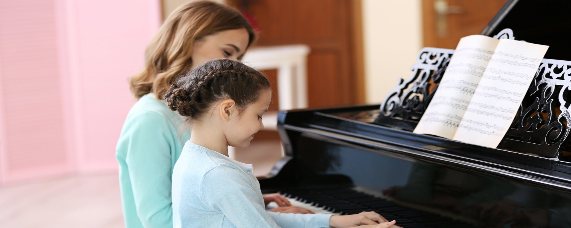 Young girl playing piano with her mother