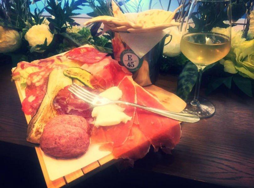 un tagliere con dei salumi,zucchine grigliate, delle piadine e un  bicchiere di vino bianco