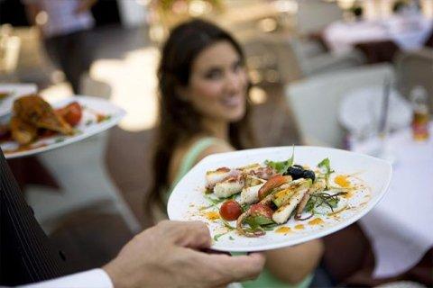 cameriere serve piatti a tavola