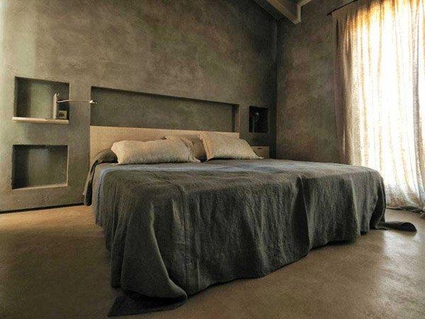 camera da letto con microcemento resinato grigio e tenda trasparente