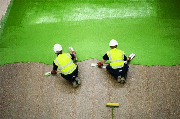 due operai mentre applicano un rivestimento verde sul pavimento