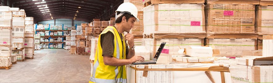 A man in hard hat and yellow high-vis clothing, using a laptop in a large warehouse