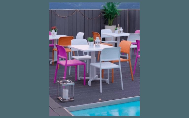 tavolini bianchi con sedie colorate a bordo piscina
