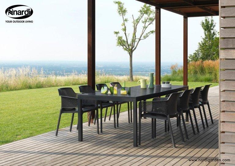 Giardino con zona pranzo con tavolo e sedie nere