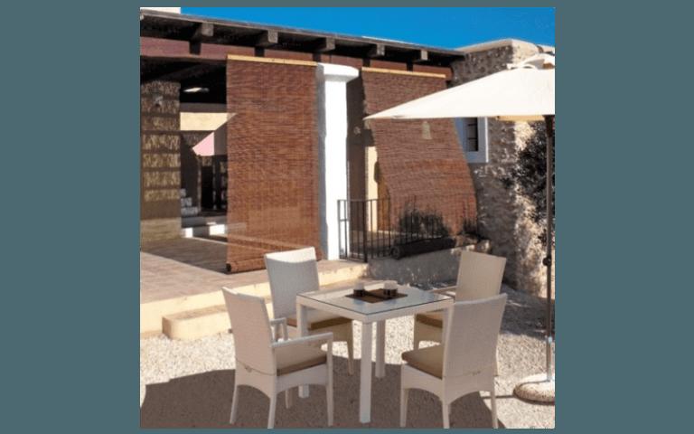 esterno di una casa con tavolino e sedie in legno bianco