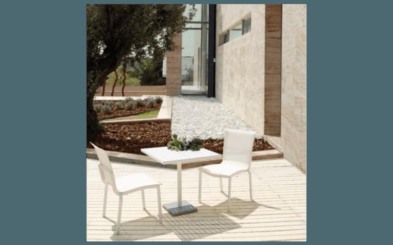 esterno di una casa con tavolino e sedie bianche