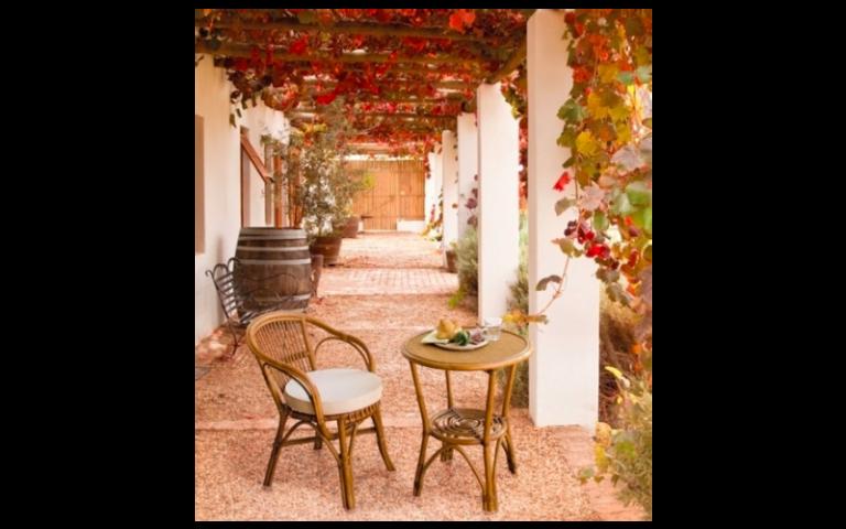 esterno di una casa con tavolino e sedia in legno