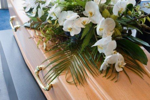 una bara in legno con dei fiori bianchi sopra