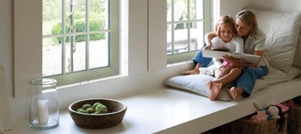 Mamma con figlia che leggono davanti ad una finestra