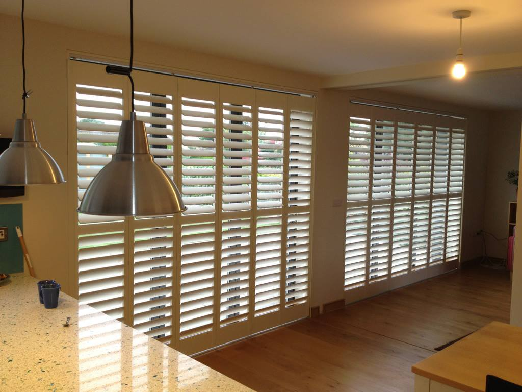 Full height wooden shutters in a kitchen