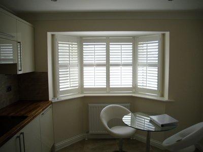 White wooden shutters on a kitchen bay window