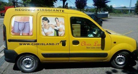 un furgone giallo con scritto Negozio Viaggiante con le immagini di un uomo in mutande e due donne che indossano della biancheria intima