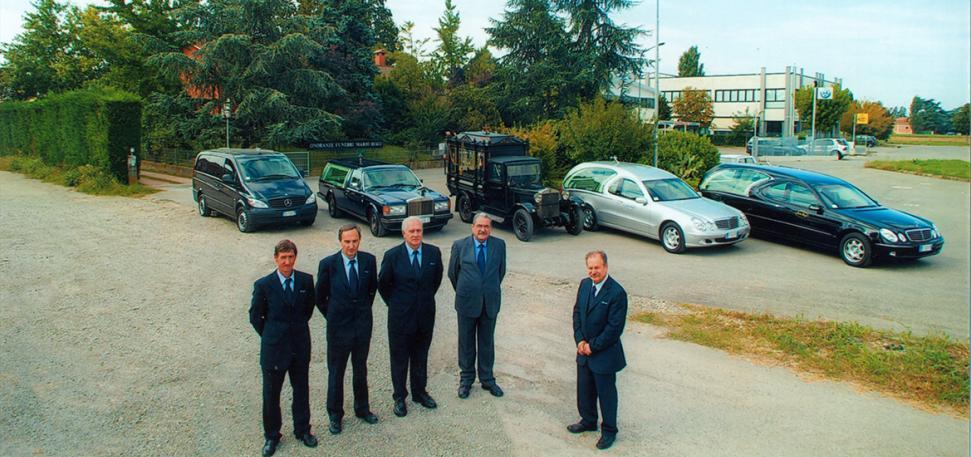 Cinque delle vetture del parco mobile della compagnia funeraria e i dipendenti accanto al padrone