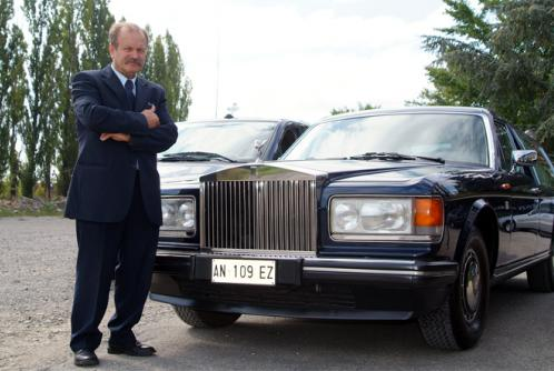 Uomo in piedi accanto un carro funerario del marchio Rolls Royce