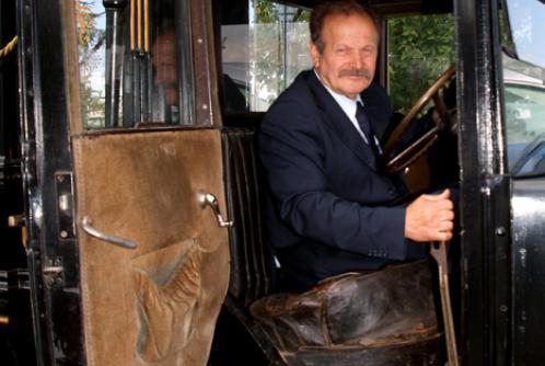 Uomo seduto all'interno de un carro funebre del secolo XX