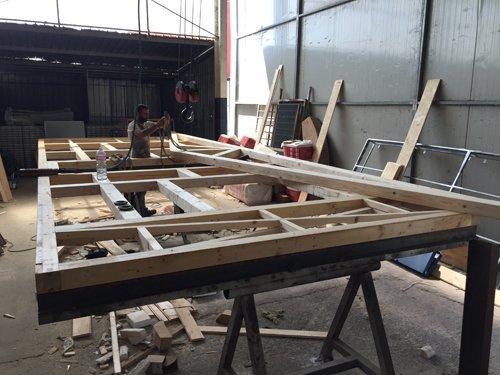 muratore mentre lavora su pezzi di legno per impalcature