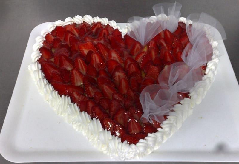 Torta a forma di cuore con panna e fragole