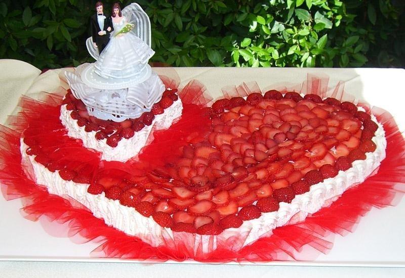 Torta nuziale a forma di cuore ricoperta di fragole