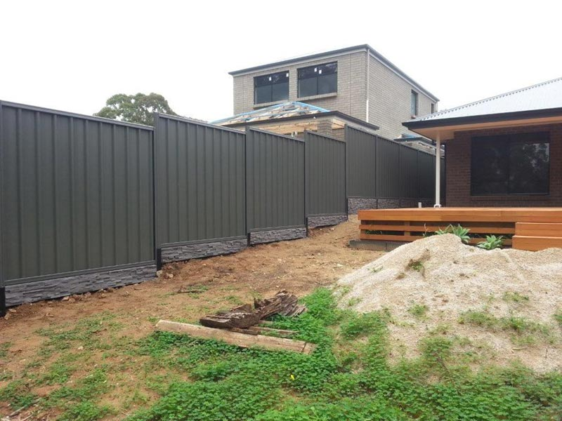 dark green fence with stone under fence