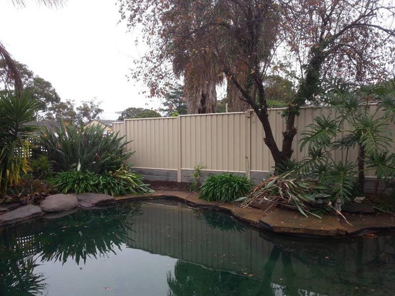 light cream fence by beautiful backyard and pond