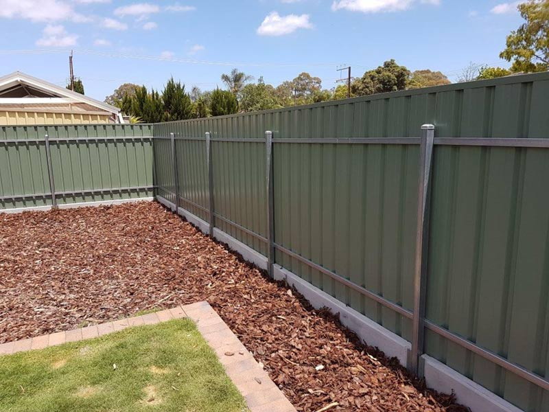 green post and rail fence with concrete under fence