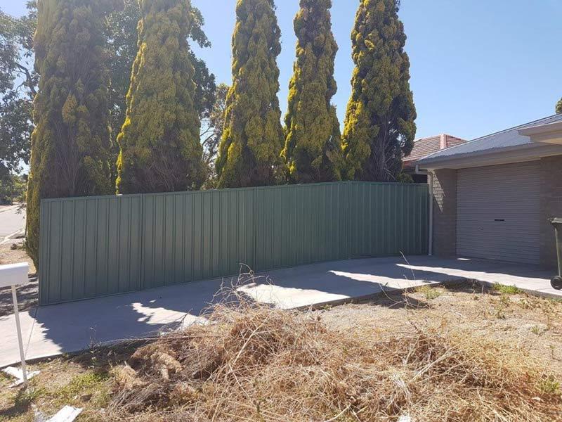 dark green fence by driveway
