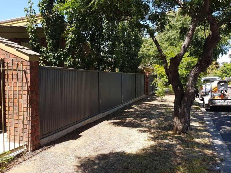 brown fence by pathway and tree