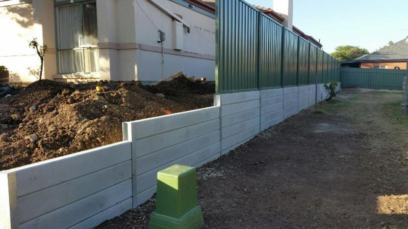 green fence with several layers of concrete under fence