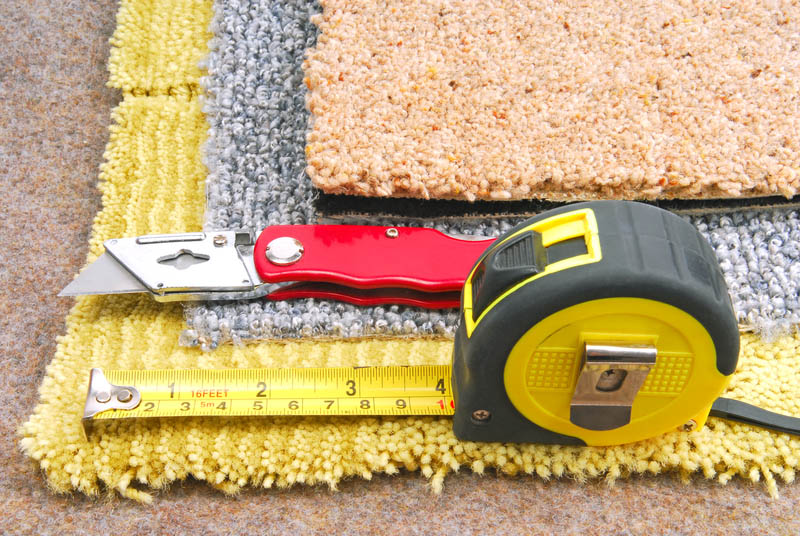 carpet swatches, tape measure and folding box cutter