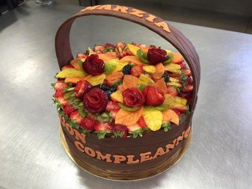 una torta a forma di cesto con della frutta assortita