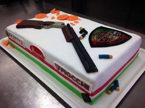 una torta rettangolare con sopra un fucile e delle pallottole