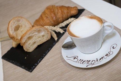 una tazza di cappuccino e delle brioches