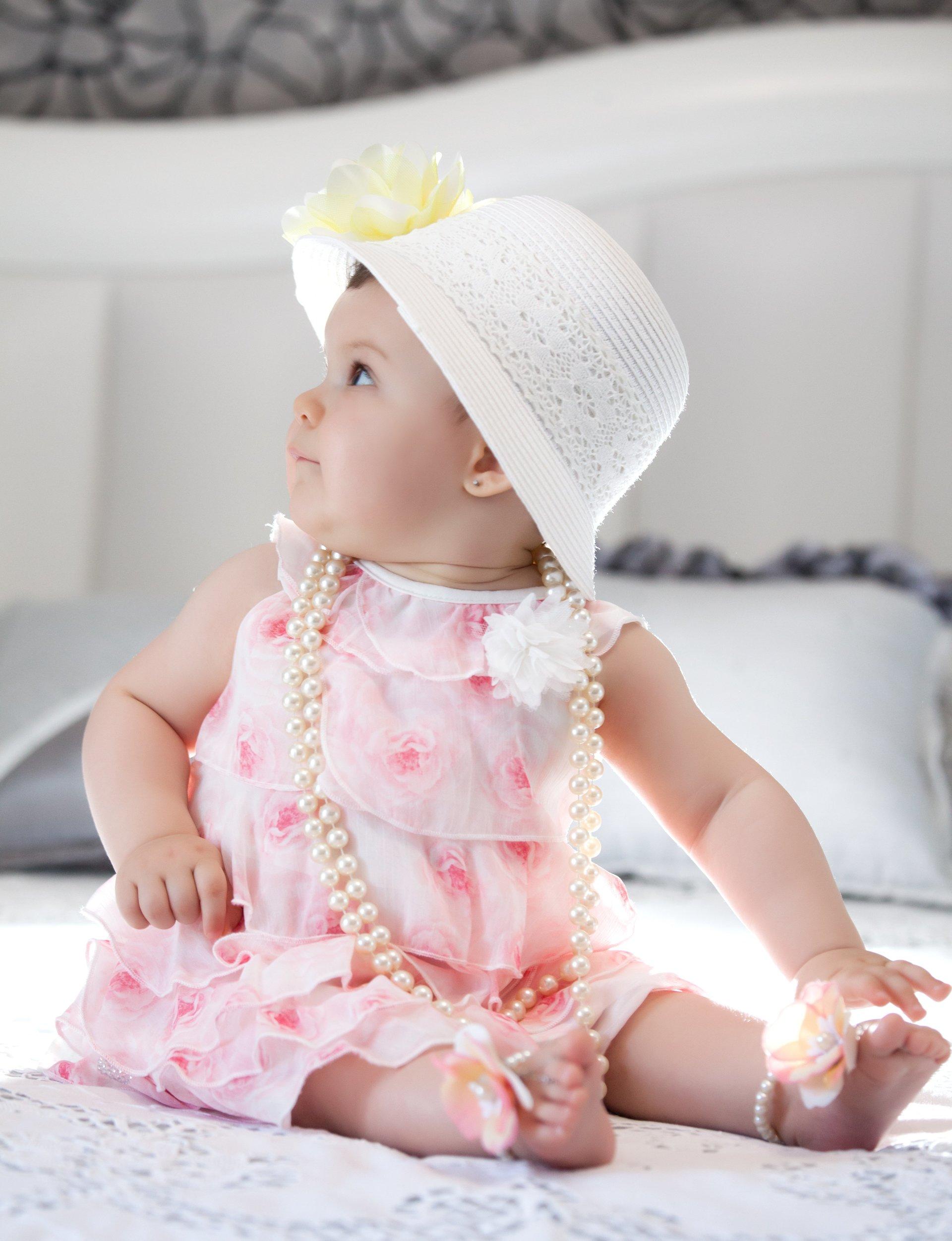 bambina su letto con cappellino bianco