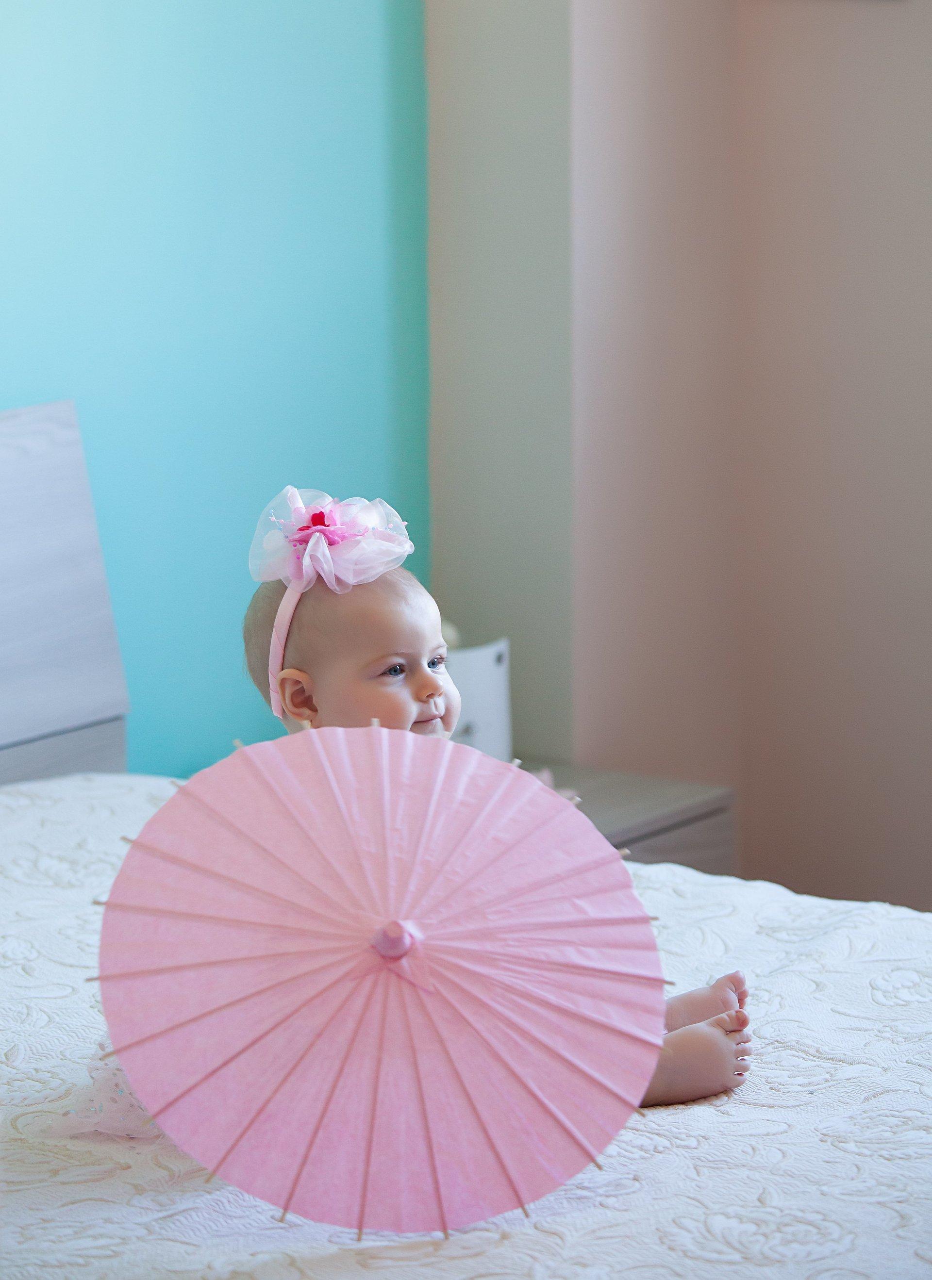 bambina su un letto con ombrellino rosa