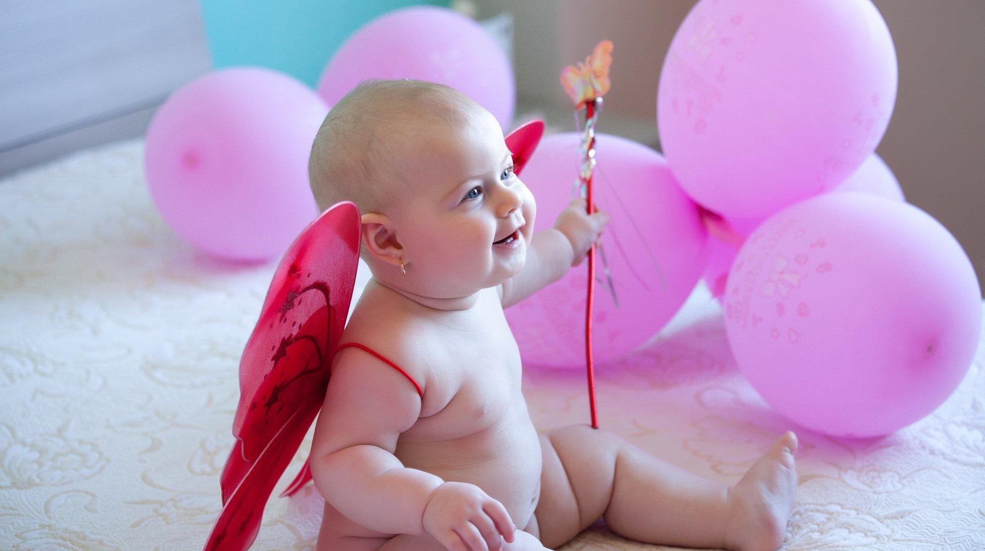 bambino con ali rosse e palloncini rosa su un letto