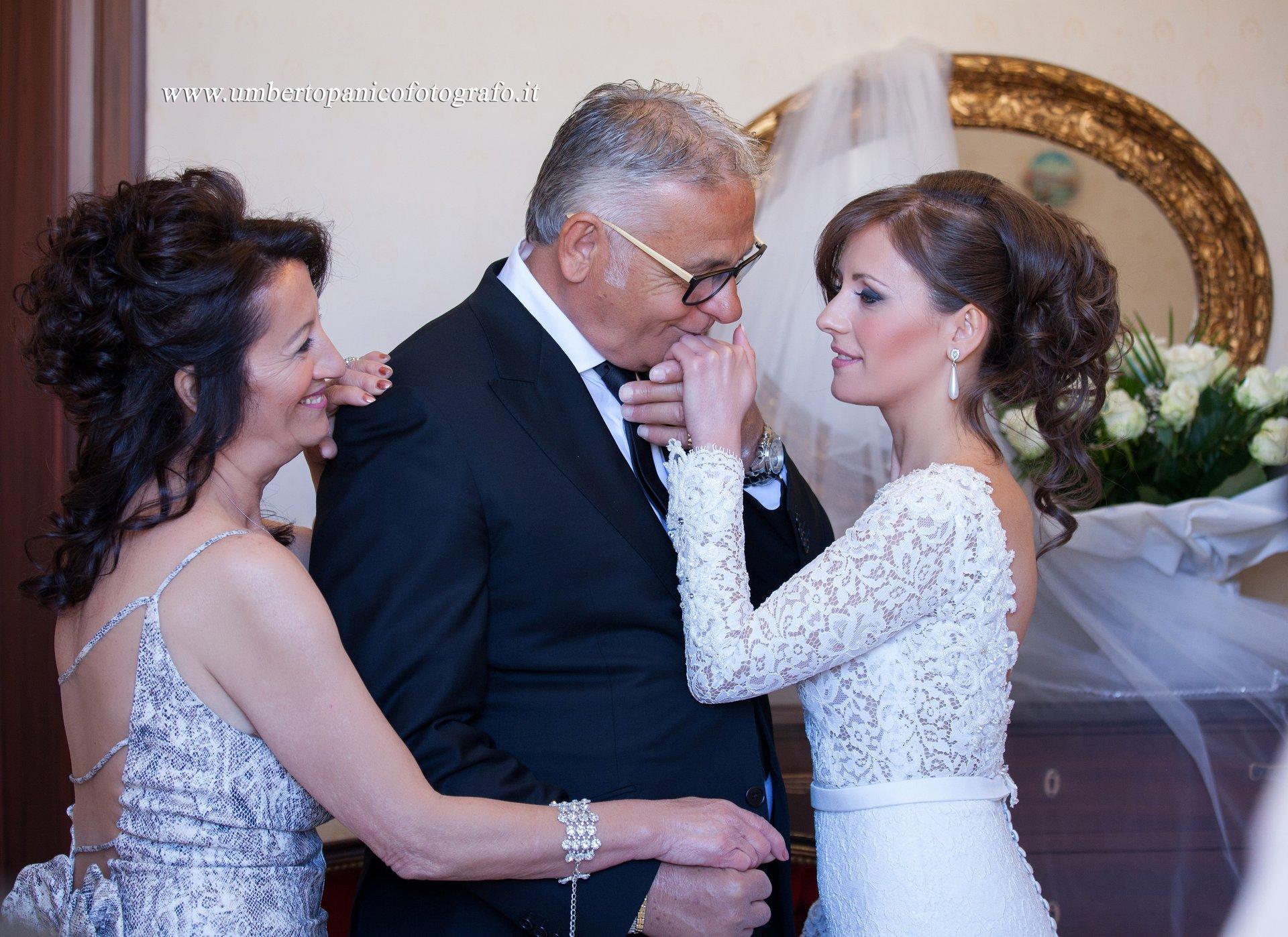 padre che bacia la mano della figlia in abito da sposa