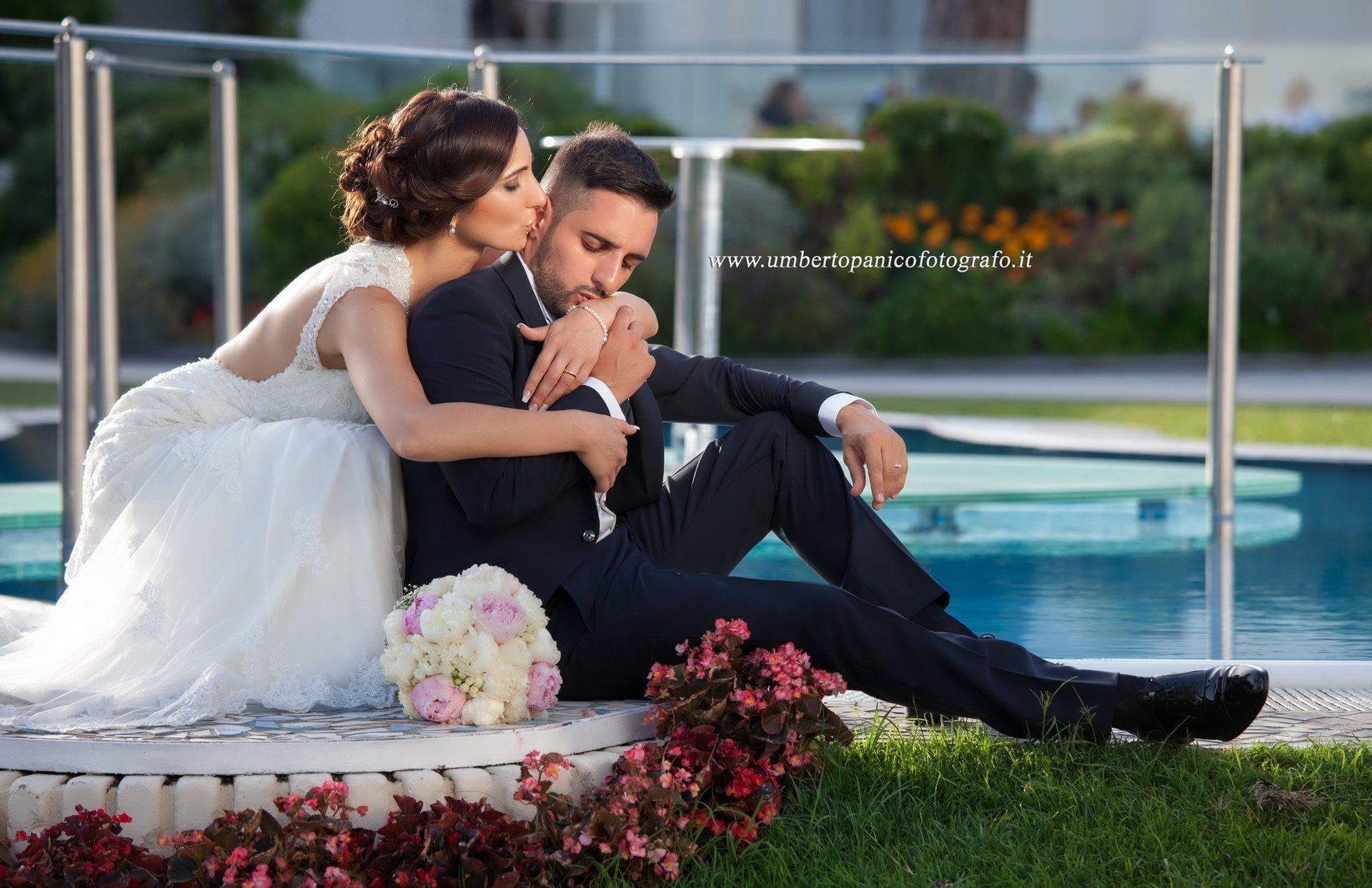 sposi seduti a bordo piscina