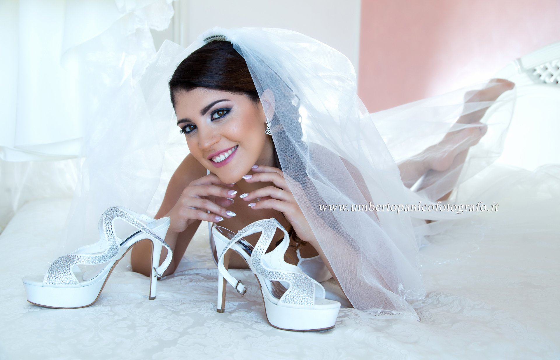 sposa distesa su un letto con scarpe in mano