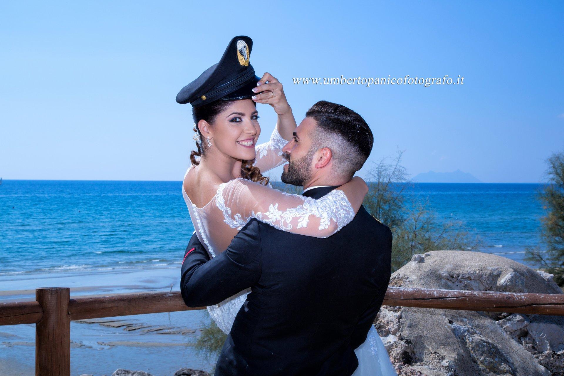 sposa in braccio allo sposo, sfondo del mare