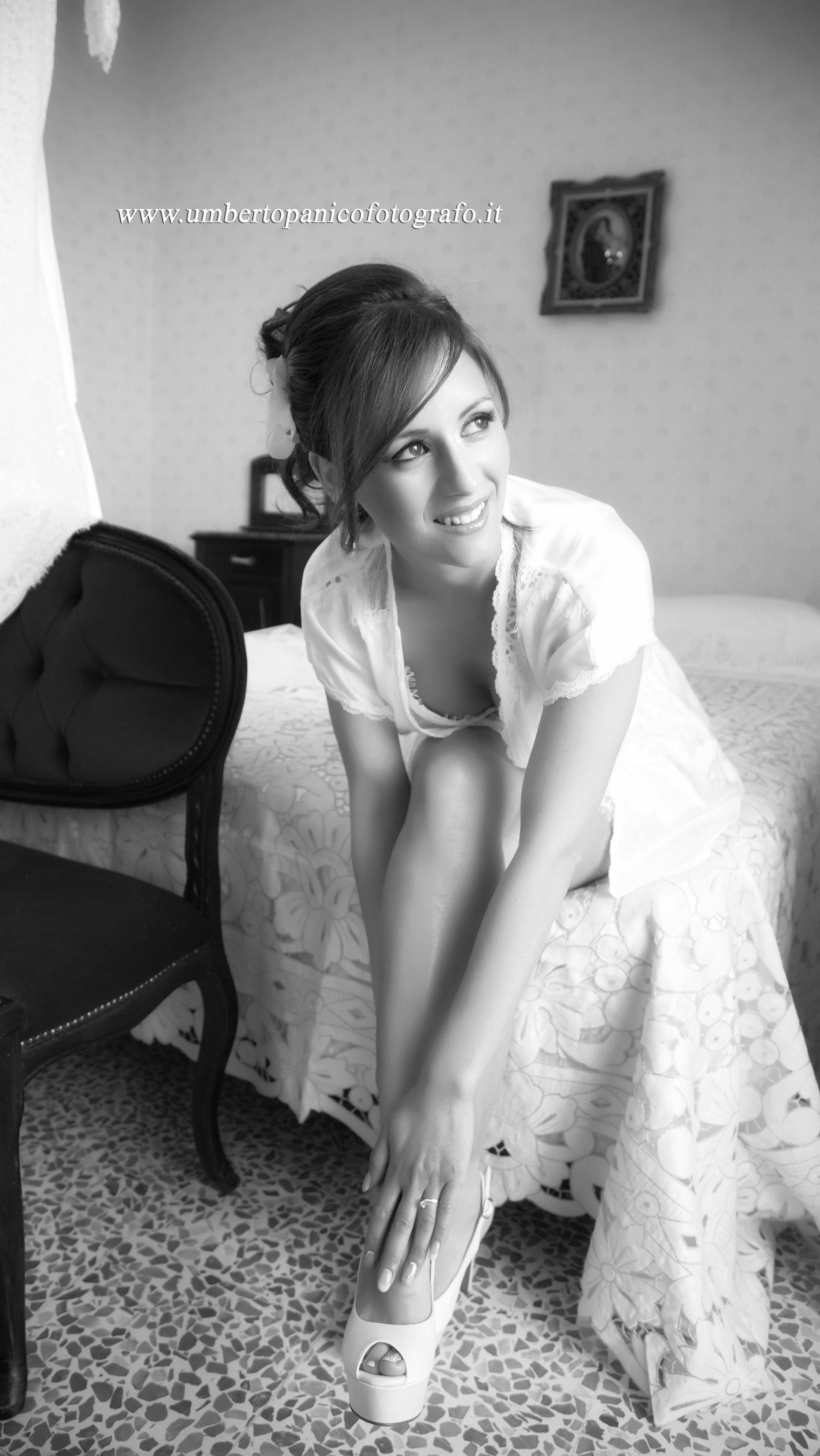 sposa sul letto che si allaccia una scarpa